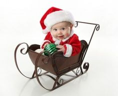 baby sitting in a metal Christmas snow sleigh holding an ornament     Stock Photo