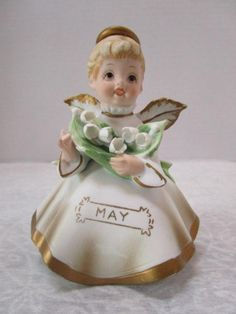 Sweet vintage May birthday figurine of little girl angel with halo and wings, carrying an armful of lily of the valley flowers from JunqueGypsy.Etsy.com.Fine details include tiny painted facial features, and draping folds of dress. Vintage Birthday Angels from Topline Imports, Japan, were popular gifts in the 60s.Unglazed porcelain with gown, halo, and wings are all trimmed in gold.Mint condition: no chips, cracks or crazing. No signs of paint wear.Original round gold sticker w/ manufacturer on Birthday Angel, May Birthday, Lily Of The Valley Flowers, Gypsy Wagon, Vintage Tupperware, Vintage Birthday, Christening Gifts, Dress Vintage, Etsy Vintage