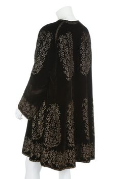 stencilled black velvet evening coat, 1920-30. with printed circular label to the satin lining, stencilled in gold with delicate foliate palmettes and bands, lined in beige/gold satin, with plaited silk tie cords to the neck