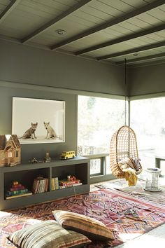 Shared boys' room features green plank ceiling adorned with green box beams over a pink kilim rug laden with toys alongside a green built-in bookcase under The Animal Print Shop Wolf Pup Pair beside a Two's Company Hanging Rattan Chairs.