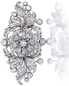 *A diamond flower brooch, circa 1840 The central flowerhead mounted en tremblant, within a stylised surround of buds and leaves, set throughout with old brilliant-cut, cushion-shaped and pear-shaped diamonds, mounted in silver and gold, principal diamond approximately 1.50 carats, remaining diamonds approximately 13.50 carats total, length 10.0cm