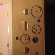 Wall bubbles  Floating round mirrors and spray painted cross stitch hoops make this bland wall so much more interesting