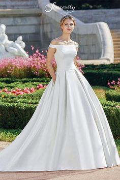 This on trend satin ball gown is everything you need on your big day. It has a portrait off the shoulder neckline and full box pleat skirt with pockets. Finish the look with a bias belt at the natural waistline and chapel length train. Formal Dresses For Weddings, Dream Wedding Dresses, Dresses For Teens, Wedding Suits, Wedding Gowns, Sincerity Bridal, Portrait, Gown Gallery, Traditional Wedding Dresses