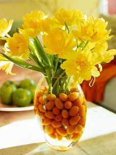 Fruit and Flower Gift for Mom - For the mom who loves bright, cheerful colors, place yellow flowers -- in this case, double yellow tulips -- in a clear vase filled with kumquats and water.