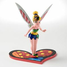 Tinker Bell Figurine designed by Romero Britto, a creative and classic piece that captures the fun and whimsy of Disney in ionic bold and colorful designs. Featuring a lovely Tinker Bell, standing on a heart, and leaning forward with curiosity.