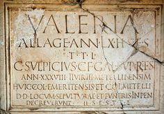 Tombstone with latin letters on a wall is located in the remains of the ancient Roman civilization of Emerita Augusta Merida, Spain.