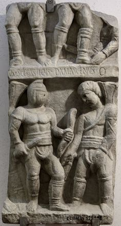 """Fighting scenes between gladitors. Luni marble. Late 3rd century A.D. Inv. No. 125598.Rome, Roman National Museum, Baths of Diocletian. A fragment of a relief of two registers, portraying gladiators fighting (retiarius and contraretiarius). The inscription on the fillet caption of the scene of the upper register conserves the two gladiators' names, Scolasticus and Damascenus. The sign """"theta"""" (Θ, theta nigrum) indicates that Damascenus died in the fight."""