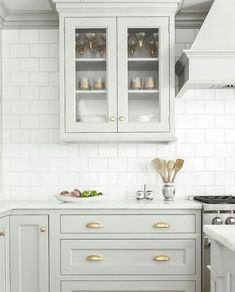 The perfect gray, with a touch of seafoam green...with gold hardware and white backsplash. Notice the double bevel on the cabinets. Perfection!! (Notice that even though there are gold hardware finishes, there is a stainless steel stove)