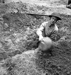 Lieutenant Ken Bell of the Canadian Army Film and Photo Unit digging a slit trench in the Normandy beachhead, France, 10 June 1944. Library and Archives Canada MIKAN 3212408