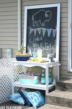 A budget-friendly patio makeover with this large DIY chalkboard.  We made over this backyard in 24 hours. Lots of blues, teals, and fresh flowers really made this space come to life. Plus the gorgeous patio furniture and new landscaping #patiomakeover #landscaping #backyard