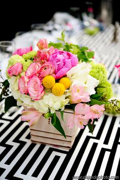 the black and white table cloth really makes this arrangement pop.