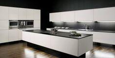 Cuisine blanche avec plan de travail noir, meubles de rangement avec fours encastrés dans le mur