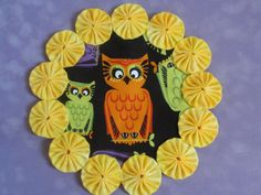 This is a cute yo yo mat featuring a bright orange owl, rimmed with handsewn yo yos in a coordinating yellow fabric. Mat/doily measures approximately 8