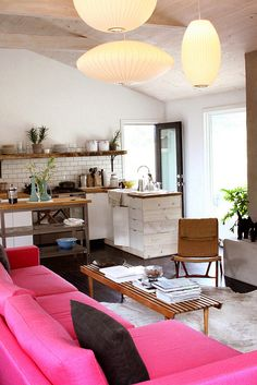 neutral kitchen, bright couch, pendant light cluster