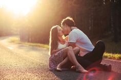 Pareja romántica besándose en la carretera al atardecer Foto Gratis