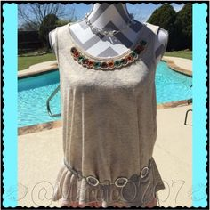 Dressy beige top by Chenault • Beige top with dressy neckline to help dress a outfit up when worn with the right accessories, or can be paired with shorts or jeans.                                                                      • Size small                                                               • Made in the U.S.A. By the brand Chenault      •Made of 53% viscose and 47% Polyester.  •Trust me Ladies! You don't want to pass on this one. Chenault Tops Tank Tops