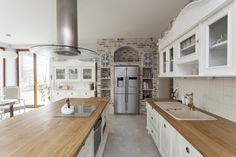 This bright tile and brick kitchen has open shelving on either side of the refrigerator. The butcher-block countertop of the kitchen island also has the ceramic cooktop.