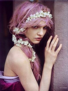 A flowered headband draws attention to cotton candy colored hair.