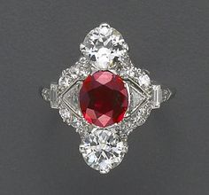 An art deco ruby, diamond and platinum ring, Raymond Yard, circa 1920 the lozenge-shaped panel centering an oval-shaped ruby flanked by triangular-shaped diamonds and old European-cut diamonds above and below, pavé-set diamonds throughout the remainder, completed by baguette-cut diamond shoulders and a plain hoop; signed Yard, Inc; ruby weighing an estimated: 1.60 carats; estimated total diamond weight: 2.00 carats.