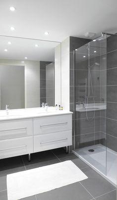 Une salle de douche avec receveur extra plat et double vasque dans un style atemporel et épuré.