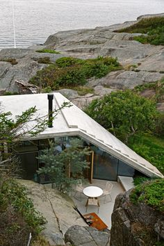 This small seaside holiday home by Norwegian studio Lund Hagem nestles against a cliff, and features a stepped concrete roof that doubles as a viewing platform