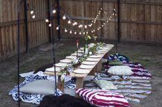 Jantar no quintal. Se não tiver mesa vale tentar montar com palets. De cadeira invista em almofadas e lençóis coloridos.