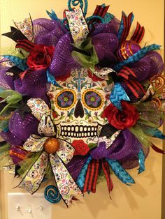 Beautiful, colorful Day of the Dead Sugar Skull deco mesh wreath. Metal skull surrounded by purple deco mesh, four types and colors of wired ribbon, two large orange and purple ornaments, two dark red roses, two orange swirl glitter picks, two turquoise swirl glitter picks, finished up with a bow made from Sugar Skull wired ribbon. Twenty seven by twenty seven by six inches deep. Very sparkly!! All decorations securely wired and/or hot glued on to two tier work wreath. As with all my wreaths…