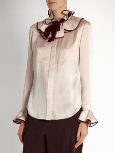 Crafted from light-pink seersucker-silk, Roksanda's Tuvala blouse exudes feminine charm. It's trimmed with purple silk-satin at the ruffled neck and cuffs for ladylike distinction, and accented with a burgundy velvet neck tie for retro appeal.