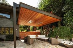 03 modern wood pergola built to one of the house's walls with a living room - Shelterness