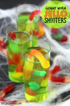 """Gummy Worm Jello Shooters - A fun kids treat perfect for mad scientist parties and Halloween! Gummy worms are suspended in green jello and the treat is garnished with a full size worm """"crawling"""" out of the glass!"""