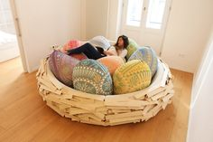The Giant Birdsnest is exactly that. Except it's not made from twigs and it's definitely not for the birds. The gigantic, cozy nest is made from a foam-padded wooden backwall that's covered with wooden panels and filled with egg-shaped cushions that allow for ergonomic sitting p