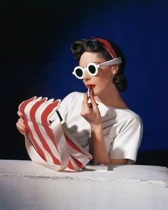 Model Muriel Maxwell in white sunglasses putting on lipstick, wearing red-white-and-blue turban, andv holding a red-and-white striped bag. Get premium, high resolution news photos at Getty Images Tim Walker, Jane Birkin, Richard Avedon, Lindbergh, Olivia Palermo, Vogue Paris, Horst P Horst, Vogue Photographers, How To Apply Lipstick