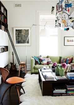 Living room with white walls, green couch, patterned pillows, wood floors, dark wood coffee table, white rug, bookshelf with black ladder, and flowers