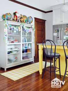 This cozy kitchen nook features a bright yellow kitchen island, a white dish cabinet and festive holiday decorations. Take a full kitchen tour on HGTV.com.