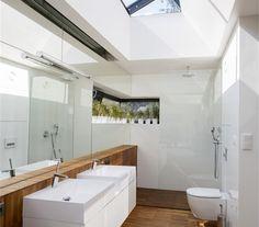 Koupelna rodičů v moderní přístavbě z litého betonu má denní světlo díky prosklení stropu a pásovému oknu. Teakové podlaze voda nevadí.