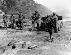 American troops blasting Yongdok with their 105-mm howitzer. 23 July 1950. Yongdok, Korea. Signal Corps Photo #8A/FEC-50-4506 (Sgt. Riley)