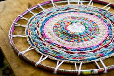 Fantastic!  I love this!  A hula hoop loom, old t-shirt as the warp, and finger knitted strand as the weft.  Great weaving and knitting project for children