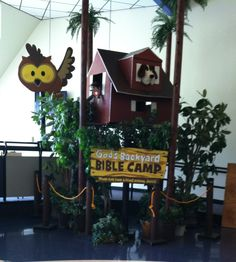 """Foam tree house made for day camp """"God's Backyard Bible Camp"""" with puppets peaking out of windows.  Large trees made out of carpet tubes.  Lots of greenery enhances the tree house."""