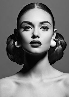 Classic beauty portrait with bold earrings and strong lines in makeup