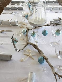Beach Christmas table with blue ball ornaments hung on driftwood branch... http://www.completely-coastal.com/2013/12/driftwood-Christmas.html