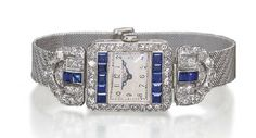 AN ART DECO SAPPHIRE AND DIAMOND WRISTWATCH, BY VACHERON & CONSTANTIN  With jewelled lever movement, the cream dial with Arabic numerals enclosed in a calibré-cut sapphire and old European-cut diamond rectangular bezel to the diamond and sapphire palmette shoulders, mesh bracelet and deployant buckle, circa 1920, 14.0 cm. Dial and movement signed Vacheron & Constantin,