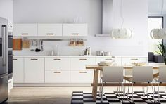 Valkoinen keittiö, jossa teräksiset kodinkoneet, valkoiset nahkatuolit ja tammiruokapöytä.