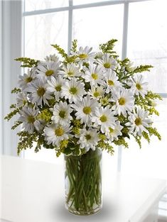 "Simple white daisy arrangement with golden rod for some yellow ""pop"".  Would look simple & cheery in mason jar with burlap or raffia ribbon."