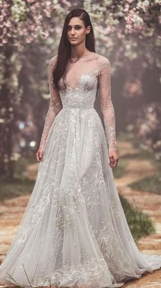 Tulle sleeved gown with nightingale embroidery and the lyrics of Sleeping Beauty's, 'Gift of Song'. Long sleeves a line wedding dress #wedding #weddinggown #weddingdress #bridedress #disneyweddinggown