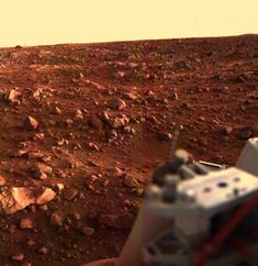 Sunset at the Viking Lander 1 Site: Color image of rocky Martian surface with portion of Viking Lander in lower right corner