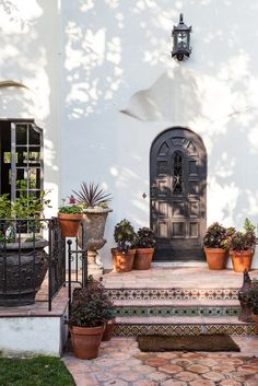 Front of Spanish style house with potted plants and tile steps