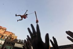 A Hindu devotee hanging from a rope throws offering towards other devotees during the Chadak ritual in Kolkata. Hundreds of Hindu devotees attend the ritual, held to worship the Hindu deity of destruction Lord Shiva, on the last day of the Bengali calendar year. Rupak De Chowdhuri—Reuters