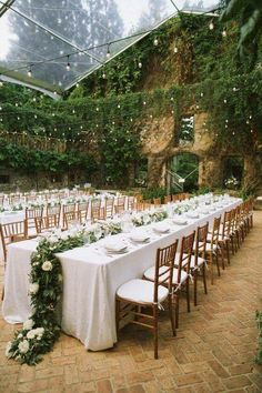 This venue's walls were already covered in ivy. The creation of a coherent look was achieved by adding greenery and white flower garlands as table runners. So pretty.