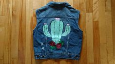 Hand painted Jean vest with an adorable cactus on it. This vest is one of a kind!  Vest is upcycled & in great condition. All thrifted jean items are washed by me before painting begins. They are painted with fabric paint, so they can be safely washed after purchase too.  Size: - Womens size medium  Measures: - about 33 inches around the waist, but can be made to about 29 inches by adjusting the straps with the buttons along the bottom back of the vest. - about 18 inches in length, (top t...