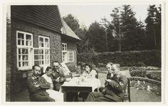 Anonymous | Duitse Luftwaffe militairen buiten aan tafel, Anonymous, 1940 - 1941 | Duitse Luftwaffe militairen, een verpleegster en een vrouw zitten buiten aan een tafel voor een huis, waarschijnlijk een oord om te herstellen. Op de achtergrond dennenbomen.